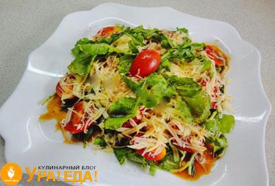 на квадратной тарелке салат посыпанный сыро и помидорами
