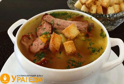суп в тарелке с ребрами и сухарями
