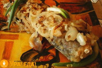жареная рыба с луком на тарелке