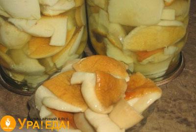 перевернутые баночки и миска с белыми маринованными грибами